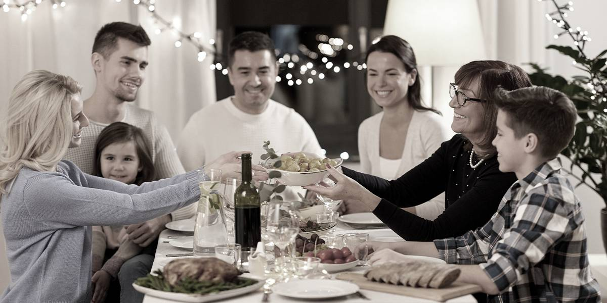Woman handing dish to a second woman over Thanksgiving dinner